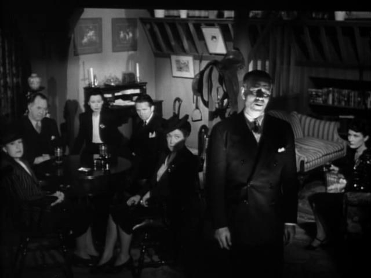 A group of Satanists sit around a table, while a man stands facing away from them, looking offscreen