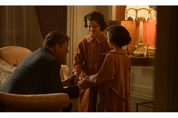 A young Margaret and Elizabeth talk with their father late at night as he sits in a chair