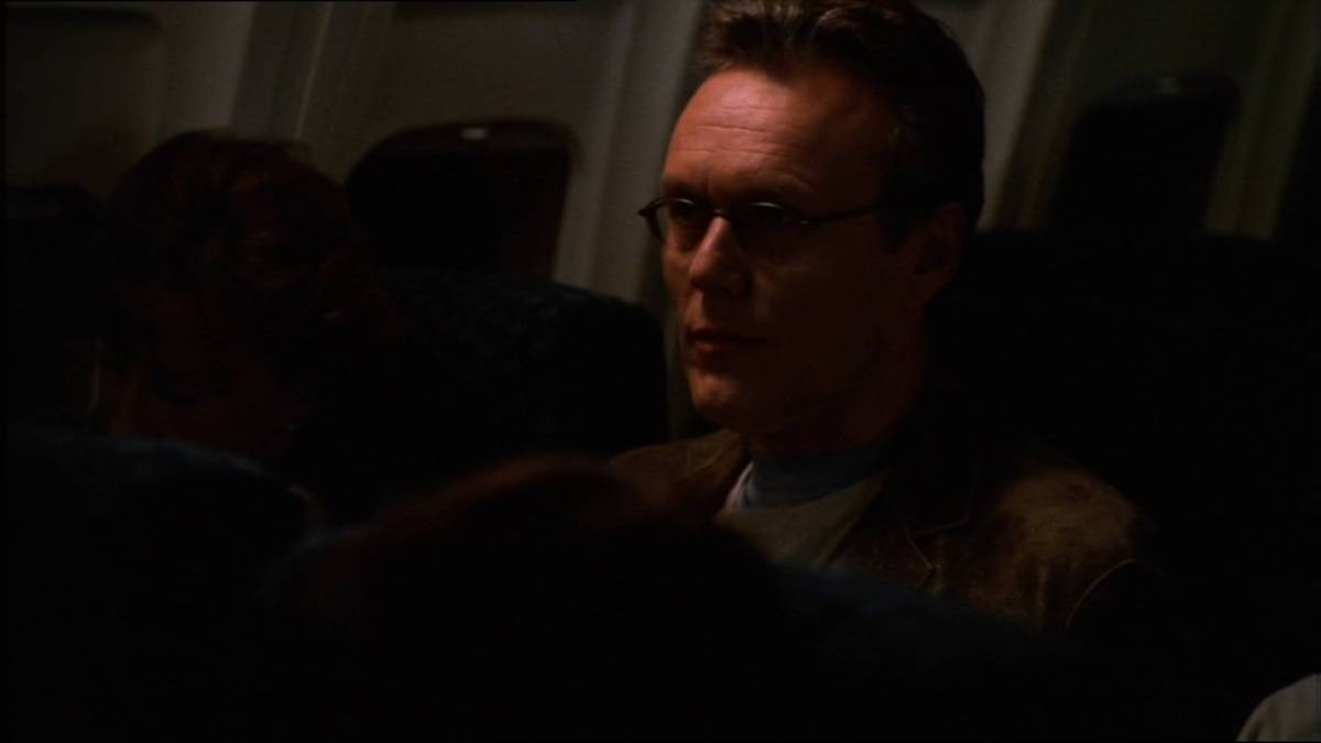 Giles sits on a plane.