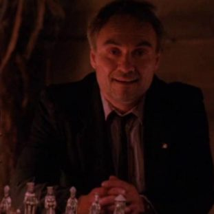 Kenneth Welsh as Windom Ealre, sitting at his table in the cabin