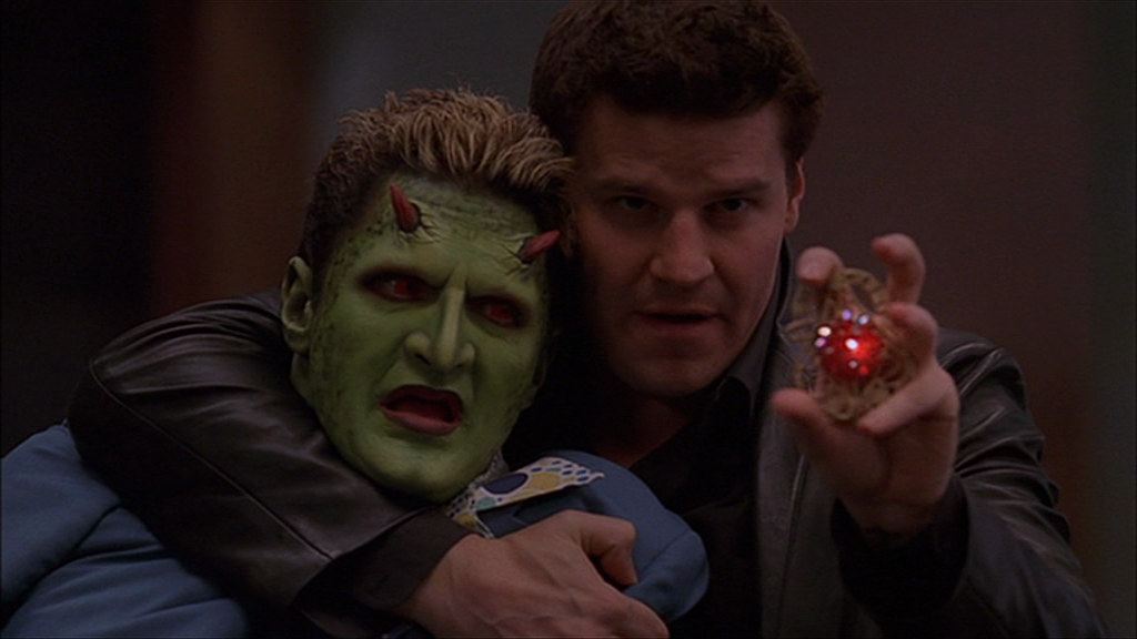 Angel has Lorne in a headlock with one arm, while he uses a jeweled amulet to cast a glamour with the other hand
