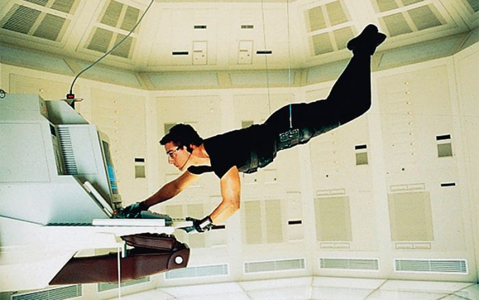 Hunt suspended from the ceiling by wires, operating a computer
