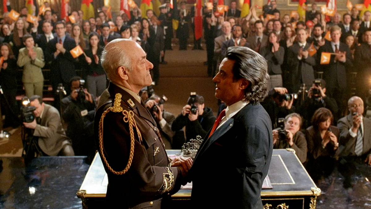 The Gath Premier and King Silas shake hands in front of an auditorium full of people