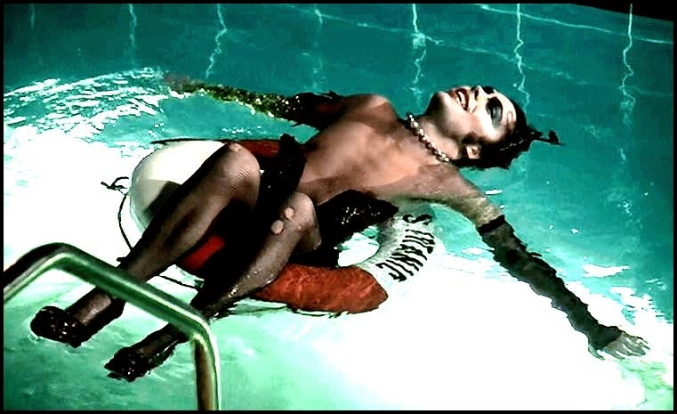 Dr Frank. N Furter laying in a swimming pool