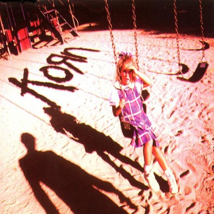 A girl in a purple dress sits on a swing, covering her eyes to look at a man, whose shadow is next to hers, both below the shadow of the name Korn.