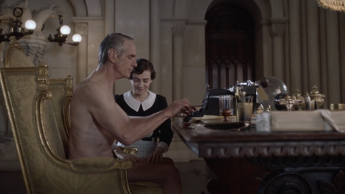 Adrian Veidt (Jeremy Irons) sits naked at his desk typing while his maid Ms Crookshanks rubs his thigh