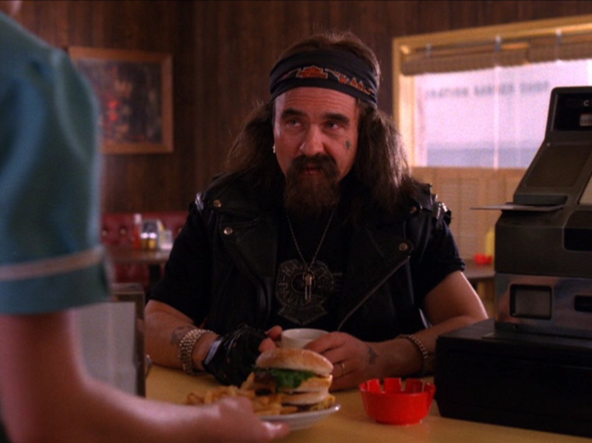 Windom Earle disguised as a biker sits at the diner counter