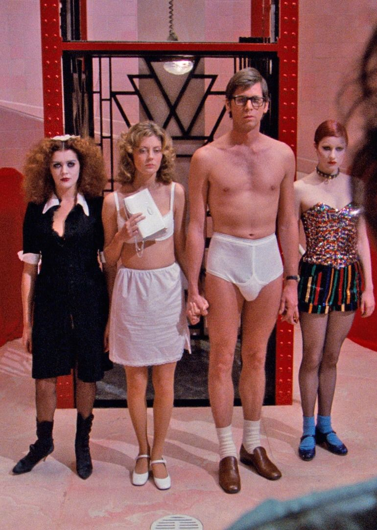Brad and Janet stand in their underwear next to Magenta and Columbia