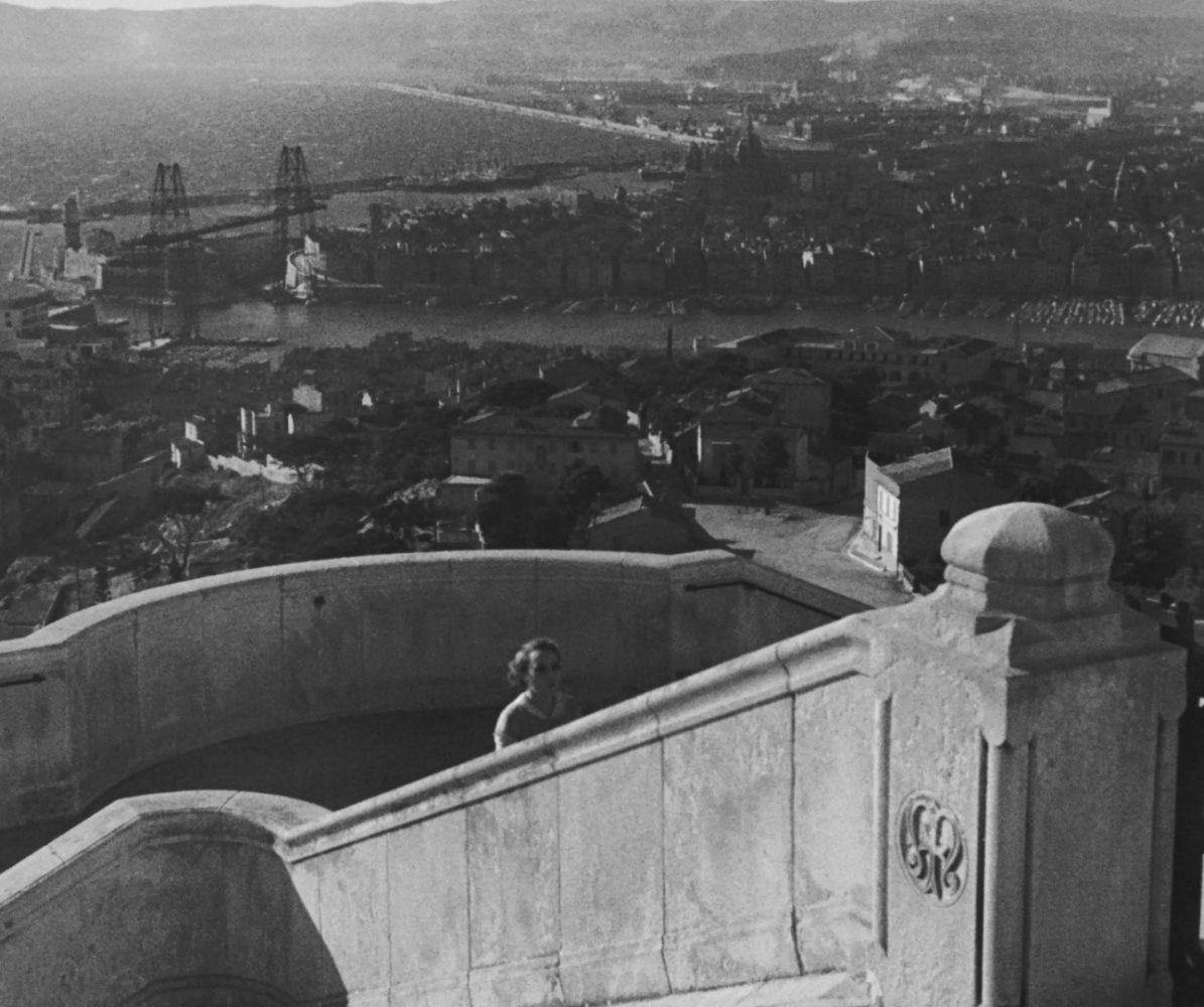 Fanny walks up church steps; in the background is a wide panorama of the port city.