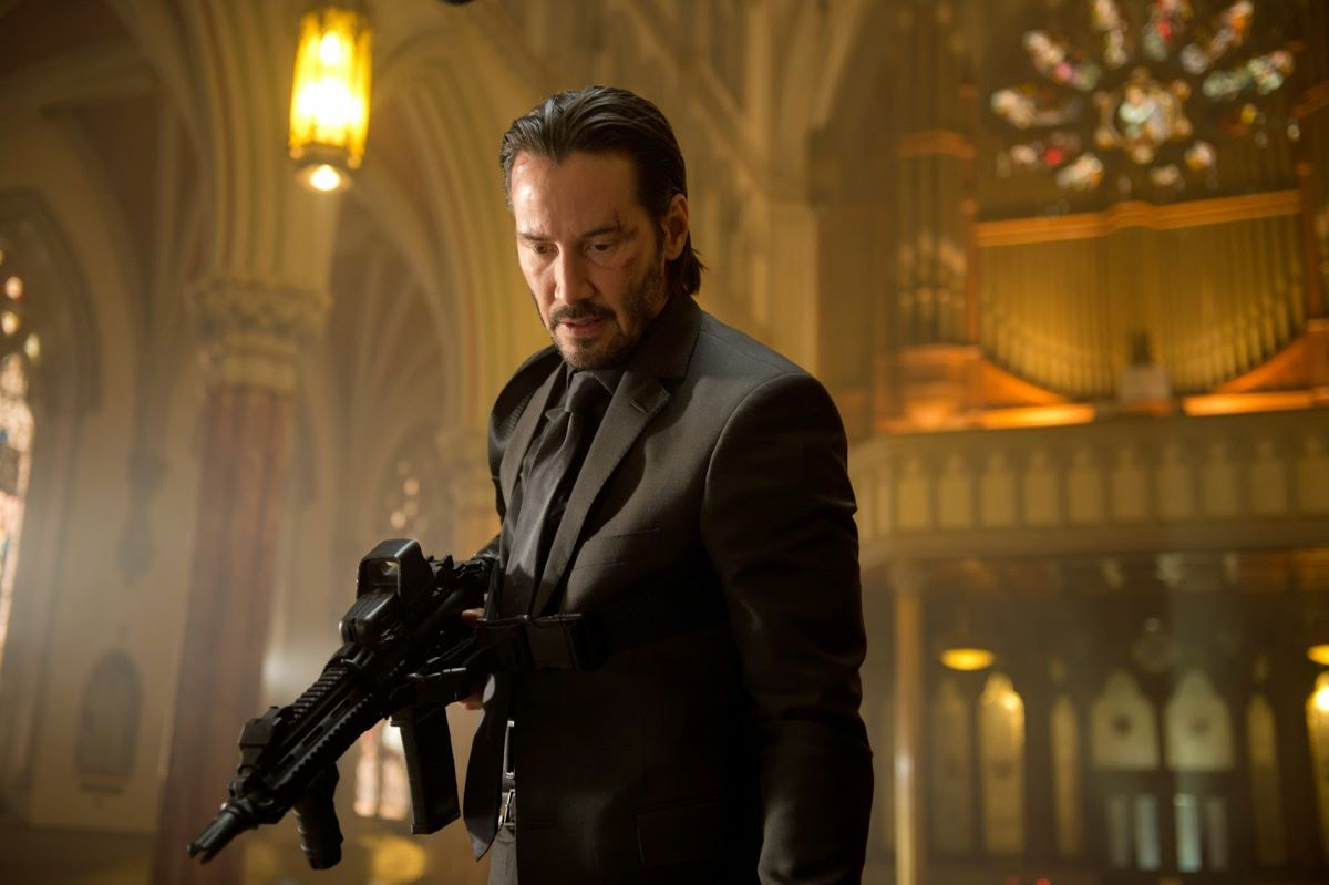 An armed John Wick prepares to do battle in a church.