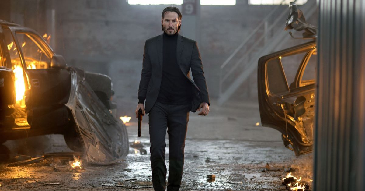 Keanu Reeves as John Wick marching through a warehouse.