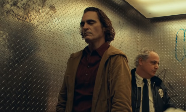 Joaquin Phoenix as Fleck, stands in an elevator with his eyes closed and a cop stands behind him