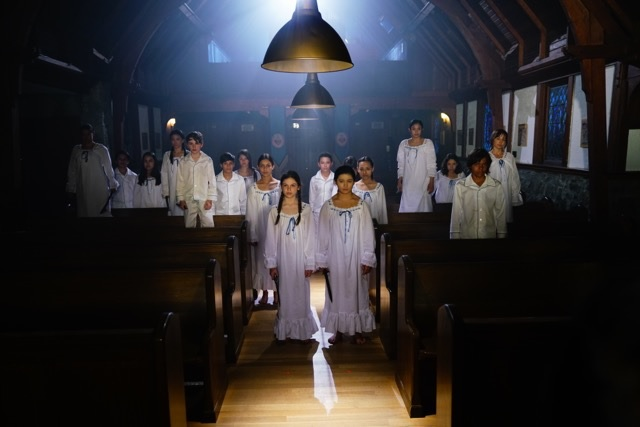 A bunch of possessed kids in white pajamas stand in a chapel.