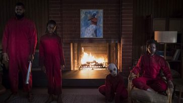 A family of a father, daughter, boy and mother stand menacingly in front of a fire place