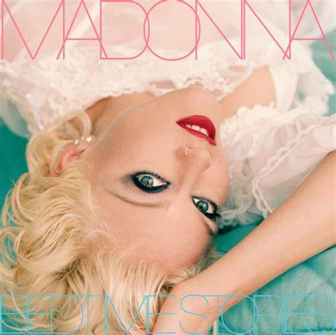 Madonna holds her arm under her head, as she lays on a pastel blue pillow. She is in a close up, upside down to our POV.