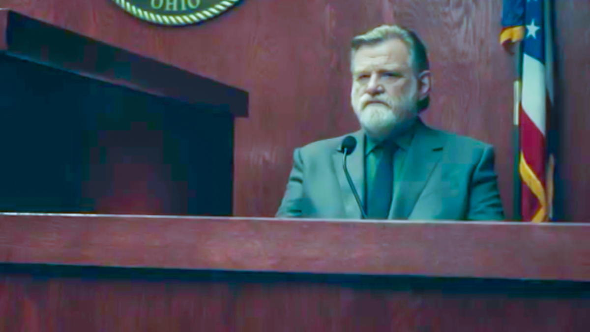 Bill Hodges sits on the witness stand, unhappy look on his face, with a US flag and Ohio seal in the background behind him.