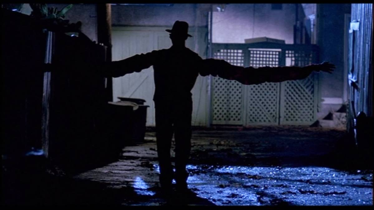 Freddy Krueger with extended arms walking down an alleyway at night