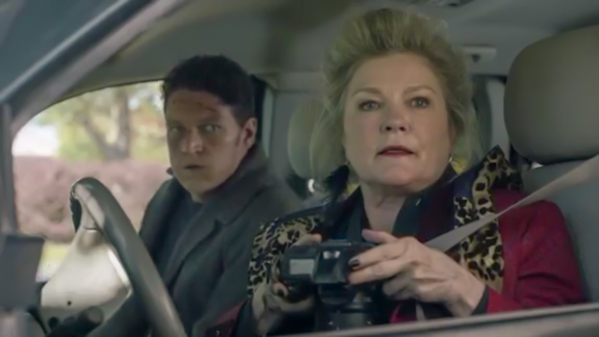 Alma and Morris sit in her car, white interior, Alma in the drivers seat with a camera pointed down, looking in the distance.