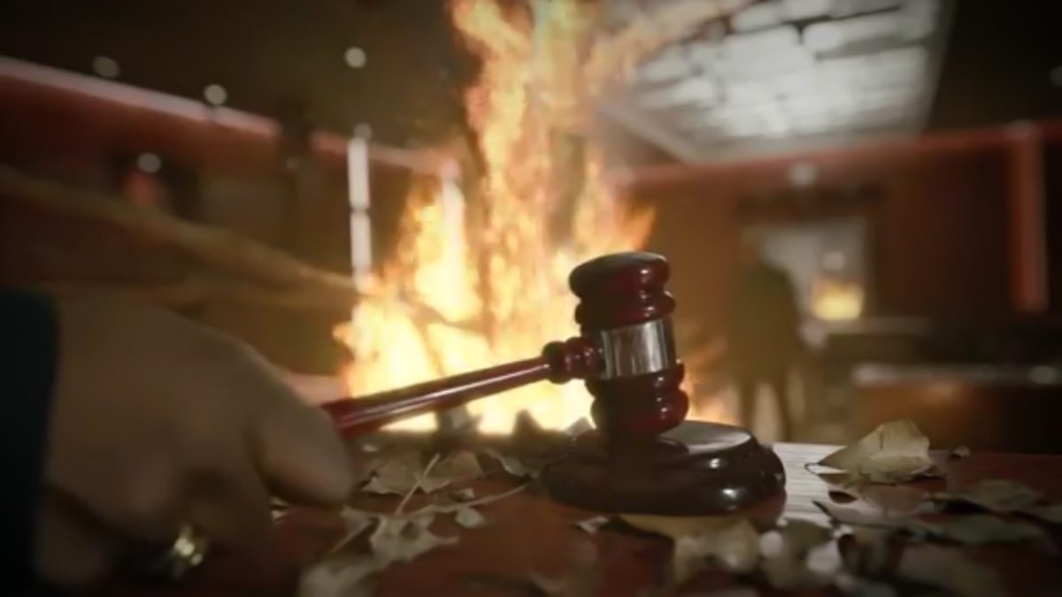 A judges gavel raps down as a tree burns in the background with a man standing beside it.