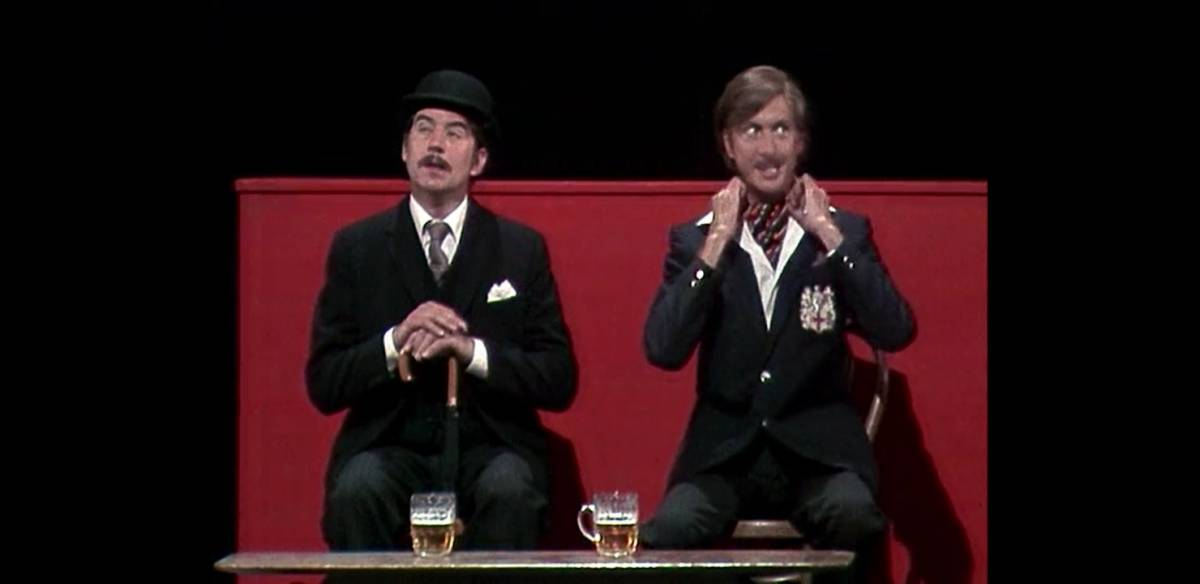 Terry Jones and Eric Idle performing on stage, dressed as a respectable man and a spin respectively