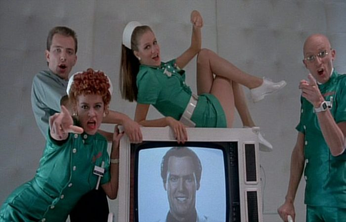 The Dentonvale staff surround a television that has Farley Flavors singing a message to Janet in Shock Treatment