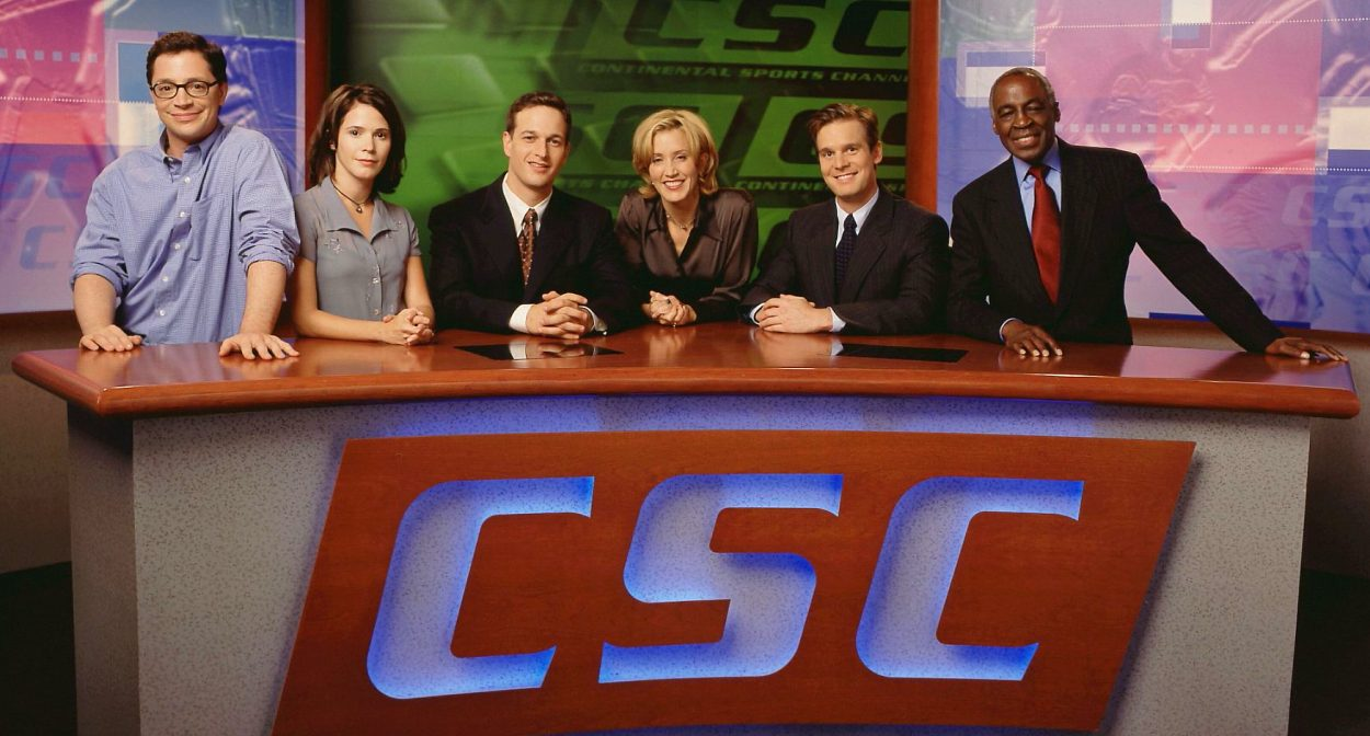 The cast of Sports Night behind the anchor desk of CSC