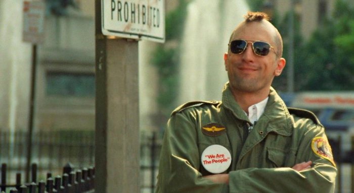 A mohawked Travis Bickle in army clothes stands and smirks while watch candidate Charles Palantine speak
