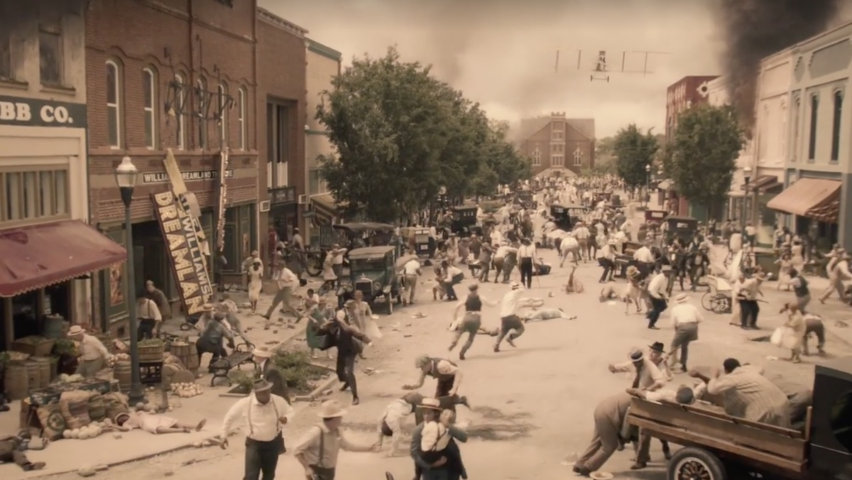 A depiction of The Tulsa Massacre in 1921, with people running through the streets