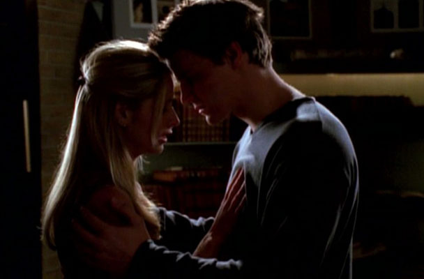 Buffy and Angel are near enough to each other that their arms and foreheads are touching. Buffy is crying and Angel is trying to comfort her.