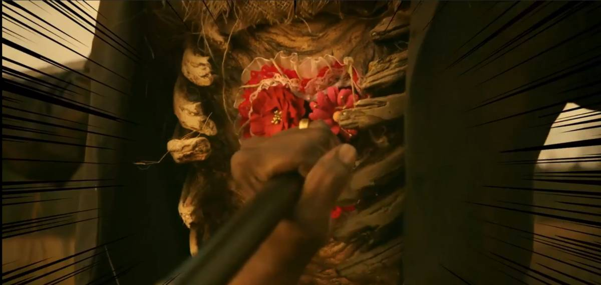 Close up of a hand impaling a cane into the embroidered heart in between a skeletal rib cage on a scarecrow.