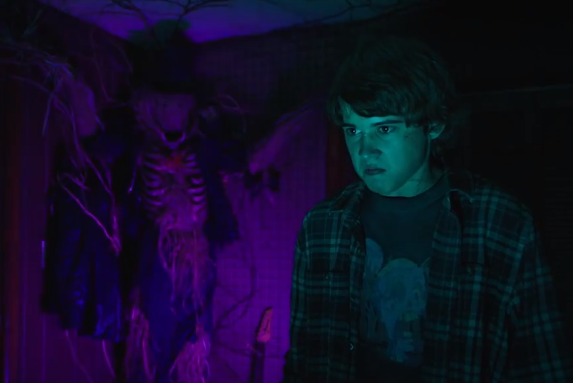 Harry looks grim and angry while the scarecrow creature looms behind him cast in purple light.