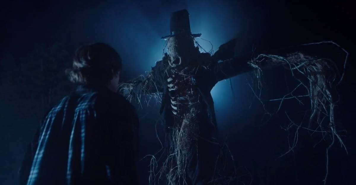 Harry's back faces the viewer as he looks up at the scarecrow creature on its mount. The scarecrow has a boar's skull for a head, long spindly hands of straw, and is backlit.