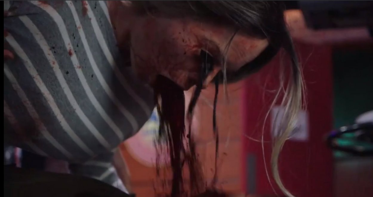 Close up shot of blood and small worms pouring out of a woman's eyes and mouth.