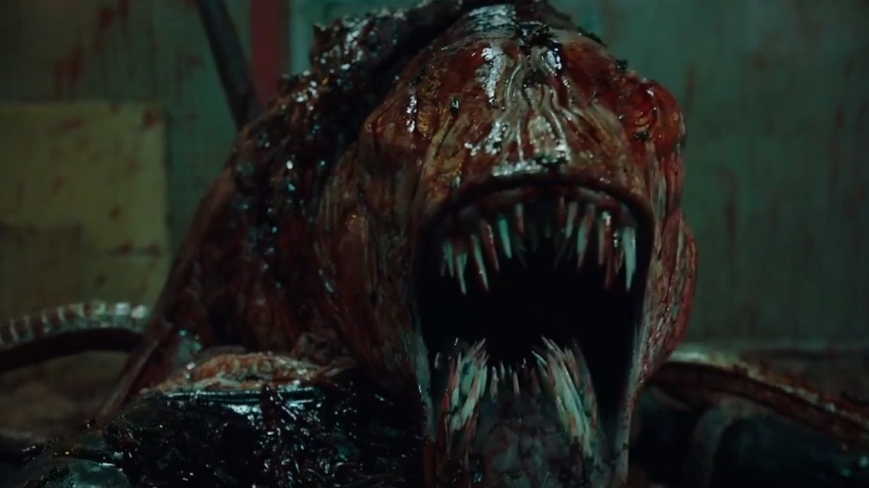 Close up shot of a bloody and grotesque monster with tentacles and rows of sharp teeth