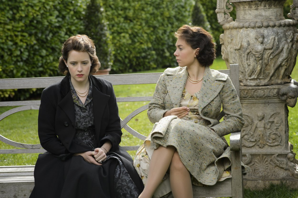 Elizabeth and Margaret sit talking on a bench on the palace grounds