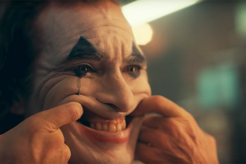Joker paints his face like a clown and lifts his lips to a grin