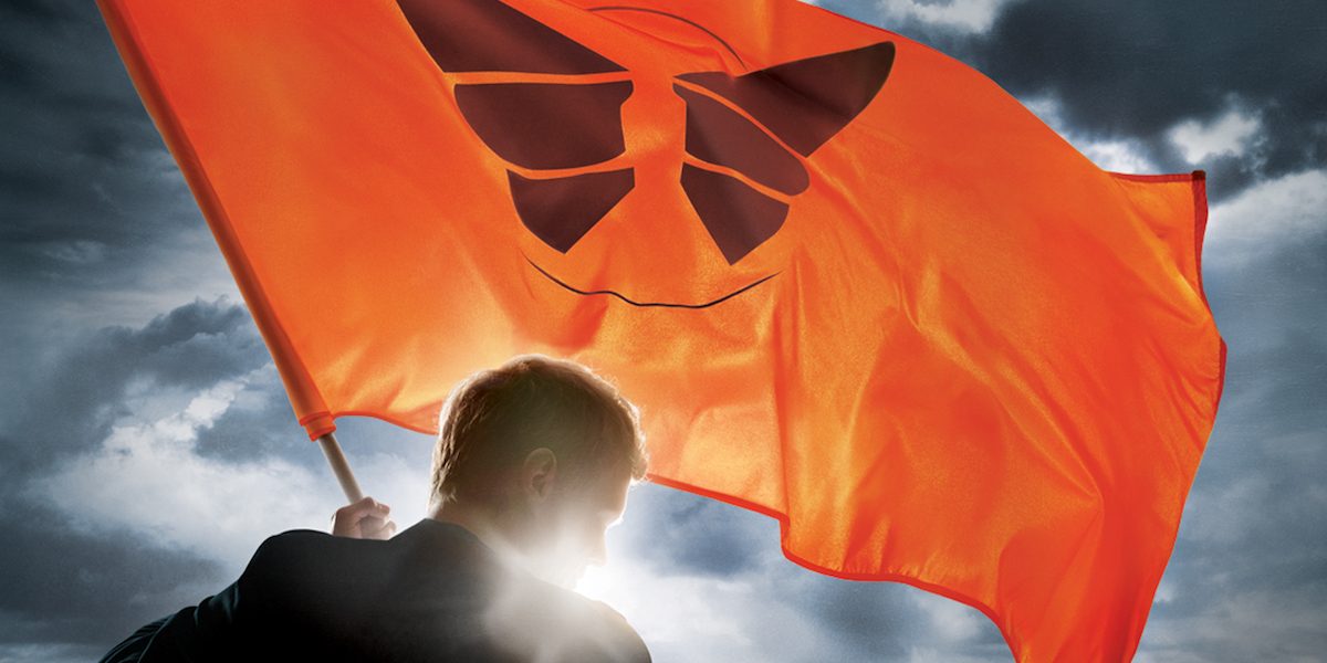 Promo photo, an over-the-shoulder shot of David holding an orange flag with a butterfly on it