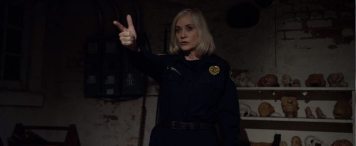 Barbara Crampton wears a police uniform and uses her fingers as a gun in The Puppet Master: The Littlest Reich