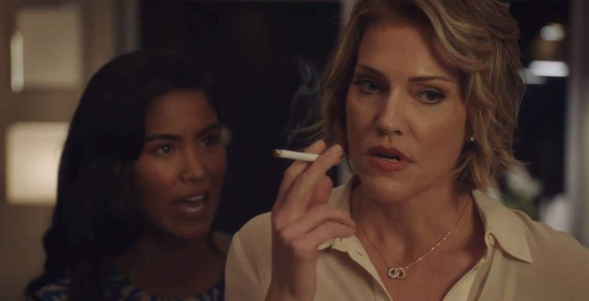 A woman smokes a cigarette and looks away while another woman talks angrily over her shoulder.