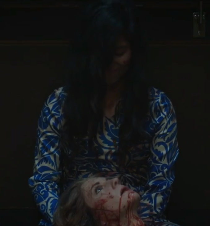 A bloody woman with eyes closed and hair in her face smiles as she holds the severed head of another woman.