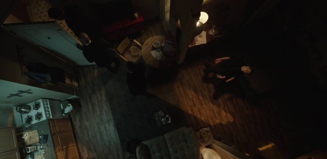Elliot convulses as he overdoses in a chair in a shot of the apartment from above