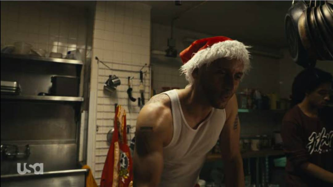 Vera wears a Santa hat in the restaurant kitchen from which he is dealing drugs