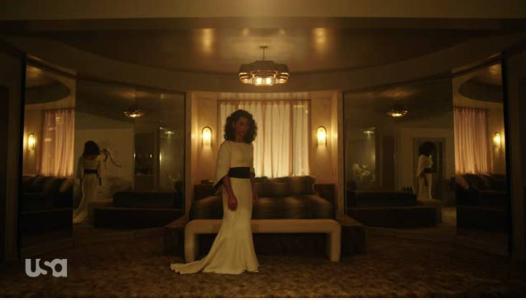 A young Whiterose wears a white dress with a black sash as she stands in front of a bed with mirrors on each side