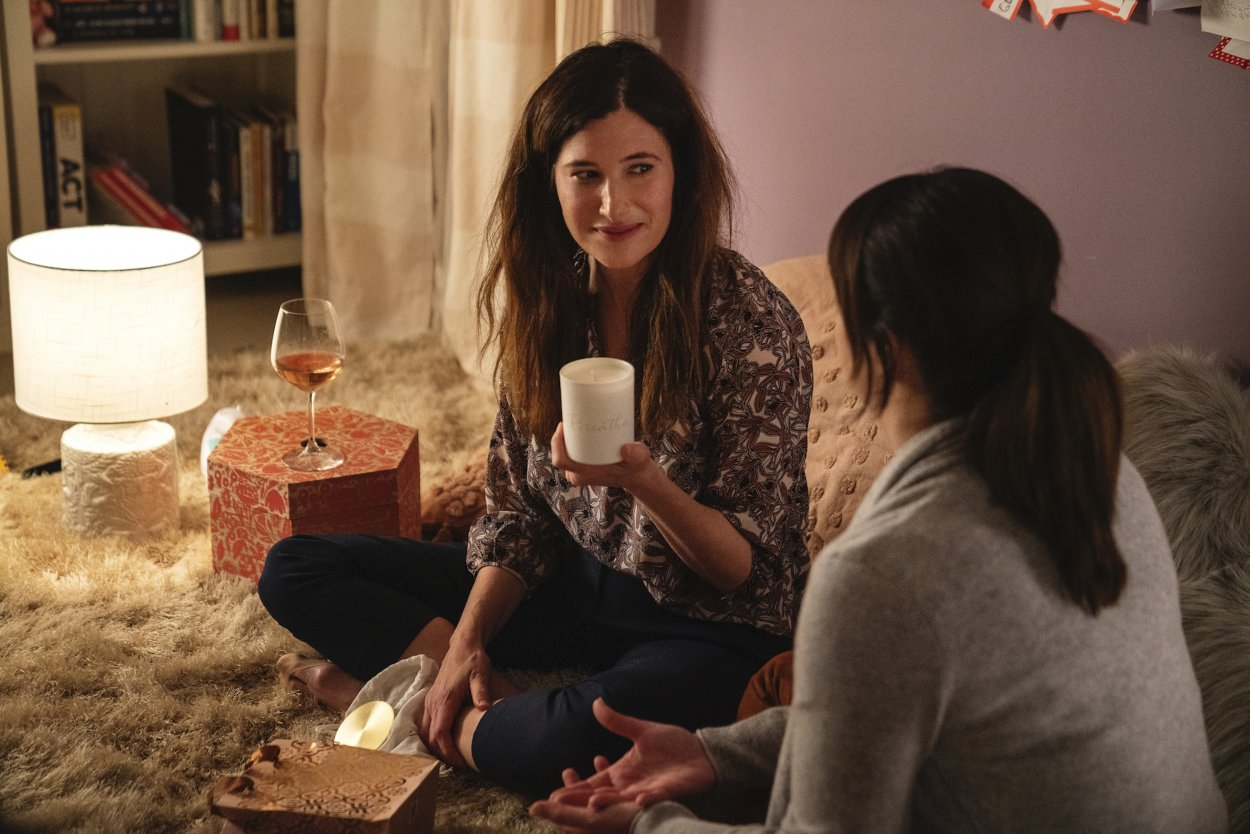 Eve sits crosslegged on the floor with Jane, holding the candle Jane bought her