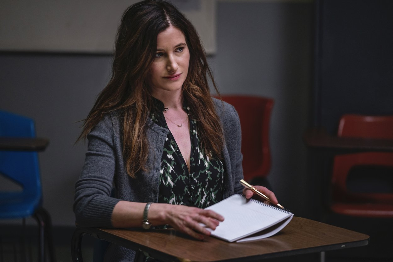 Eve sits at a desk with a notebook open in her personal essay class