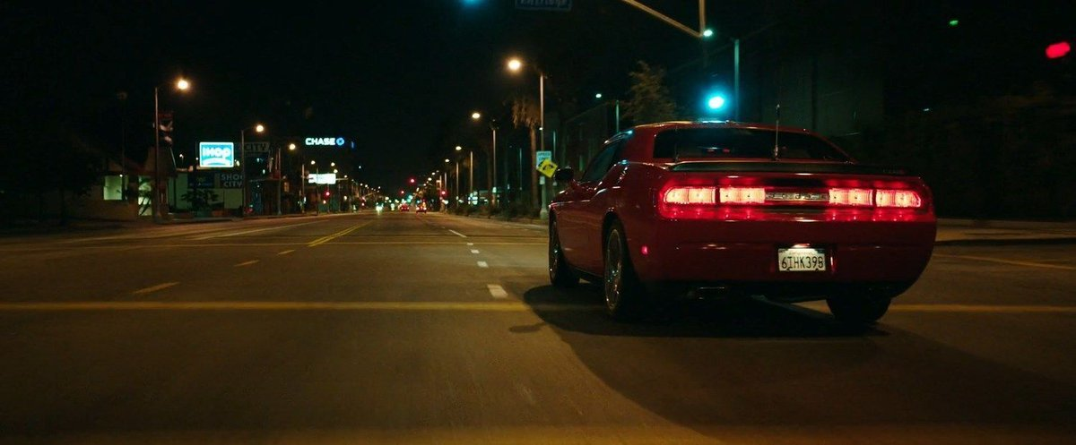 A red sports car being driven through the quiet streets of LA at night