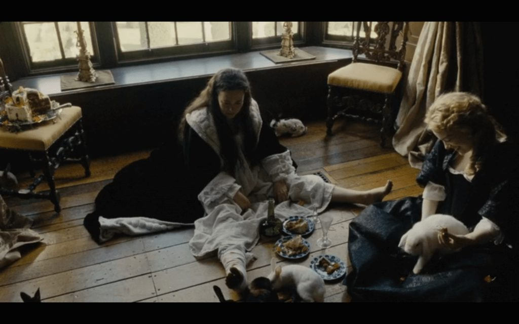 Queen Anne sits on the floor with her rabbits