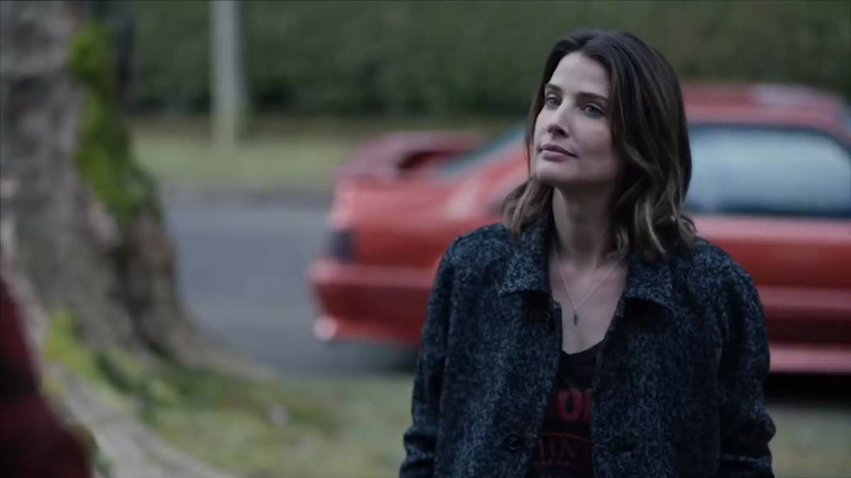 Cobie Smulders stands outside in front of a car in Stumptown