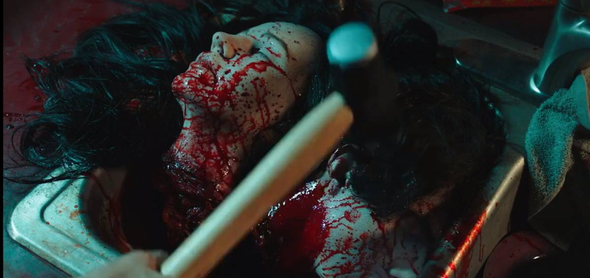 A hammer is held above two bloody severed heads.