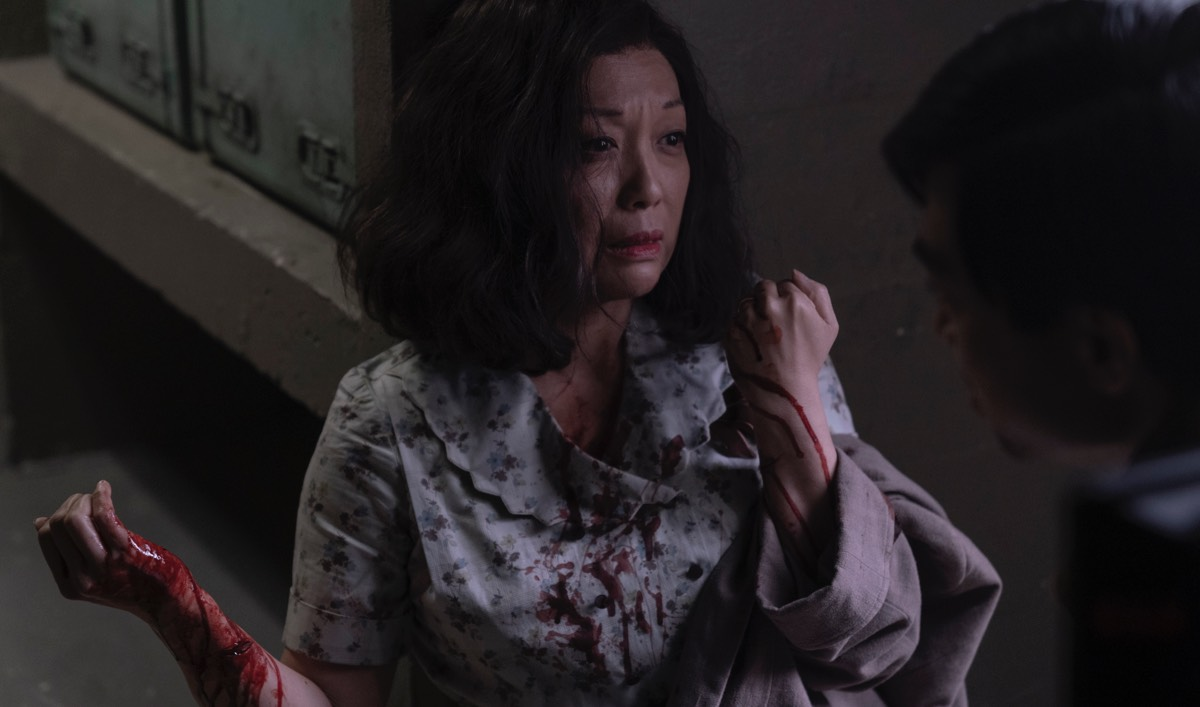 Asako looks at someone in shadow, blood dripping down her arm